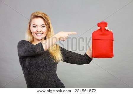Positive smiling woman recommending warm hot water bottle in red soft fleece cover, on grey. Health care, pain relievers, recovery concept.