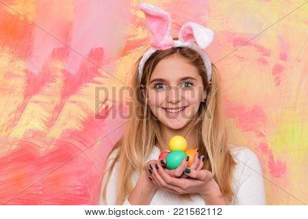 happy easter girl ears with colorful painted eggs, has adorable smiling face and long blonde hair in pink bunny on abstract background. traditional spring holiday celebration, copy space