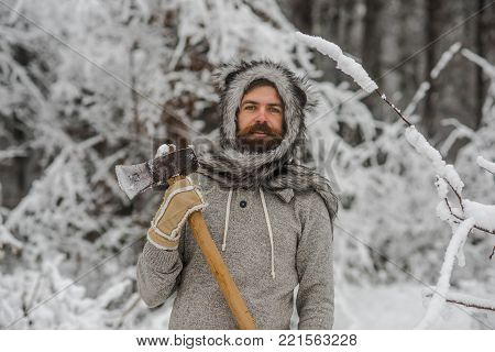 Camping, traveling and winter rest. Man lumberjack with ax. Bearded man with axe in snowy forest. skincare and beard care in winter, beard warm in winter. Temperature, freezing, cold snap, snowfall.