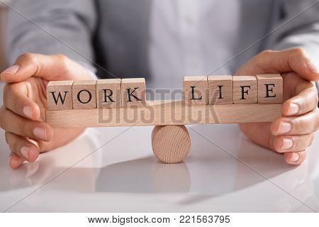 Businessperson's Hand Covering Balance Between Life And Work On Wooden Seesaw In Office