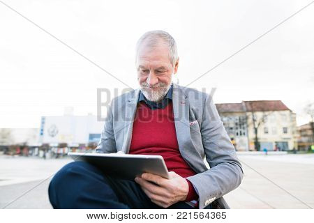 Handsome senior man in town sitting on bench, working on tablet.