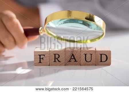 Person Examining Fraud Blocks Through Magnifying Glass On White Desk