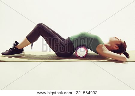 Front view of a young woman stretching body in gymnastics class. The body stretching exercise for women can help for sports, gymnastics, dance. The body flexibility is important for sports, gymnastics.