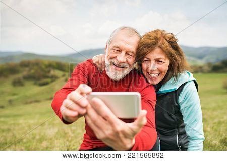 Active senior runners outside on the green hills taking photo with smart phone. Calvary in Banska Stiavnica, Slovakia.