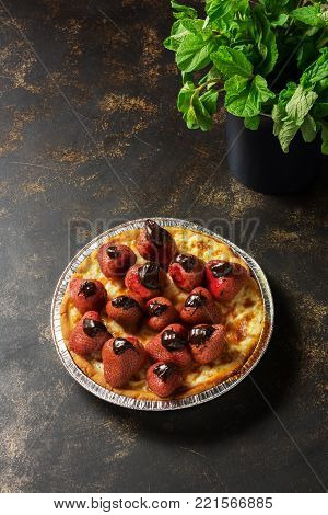 Pie baked with strawberries, a bowl with mint leaves on a dark background