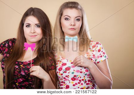 Two women holding carnival accessoies on stick having fun wearing tshirts with flower pattern.