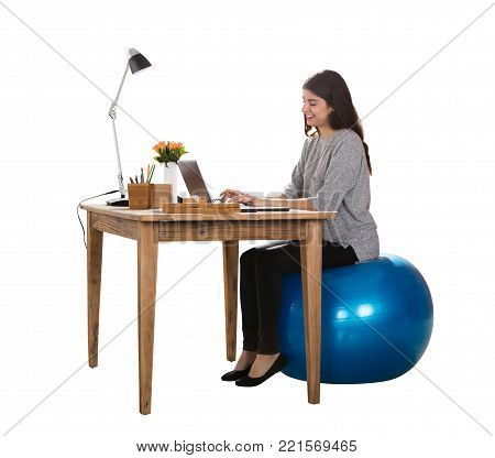 Happy Young Woman Sitting On Pilate Ball Working On Laptop
