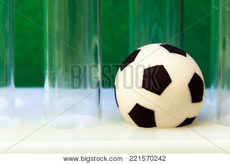 Macro. Medical scratched test tubes and a souvenir soccer ball on a green background. Concept money and sports, medicine and football, corruption and doping. Super close-up. poster