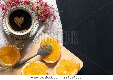Coffee with heart shape and bread with jam - Breakfast with a cup of coffee with a foam heart, bread slices smeared with peach jam on a cutting board, surrounded by flowers, on a black table.