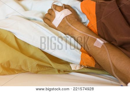 close up of saline solution on hand of man patient lying on the hospital bed,drop of saline solution to help patient poster