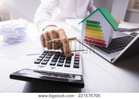 Businessman Calculating Financial Data With House Model On Laptop Showing Energy Efficiency Rate In Office