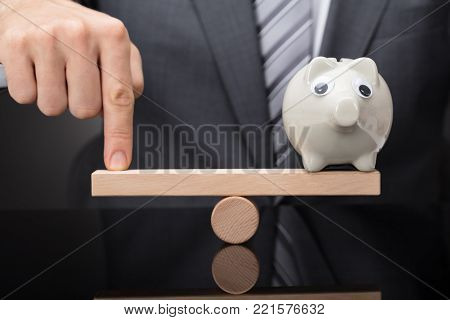 Close-up Of A Person's Finger Balancing Piggy Bank On Wooden Seesaw