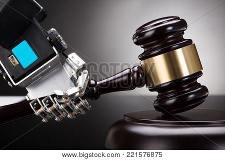 Close-up Of A Robot's Hand Striking Gavel On Sounding Block Against Grey Background