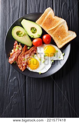 Homemade Fried Eggs With Bacon, Onion, Avocado, Toast And Tomatoes Close-up On A Black Plate. Horizo
