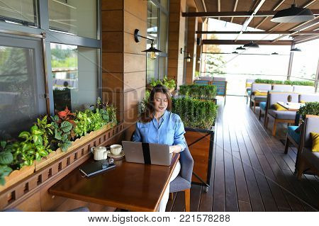 Female student chatting with friends by laptop at cafe. Young girl dressed in jeans shirt sitting near window with room plants. Concept of communicating with close people and modern technologies.