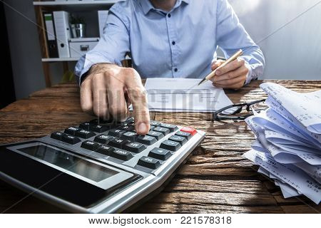 Close-up Of A Businessperson's Hand Calculating Invoice With Calculator At Workplace