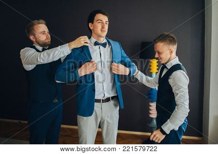stylish groomsmen helping happy groom getting ready in the morning for wedding ceremony. luxury man in suit in room. space for text. wedding day.