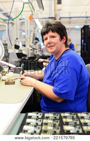 production and assembly of microelectronics in a hi-tech factory - older woman assembles components