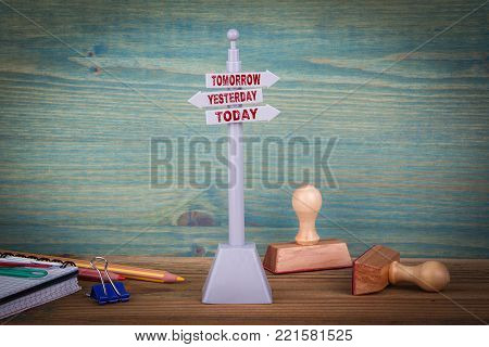 tomorrow yesterday today. Signpost on wooden table.