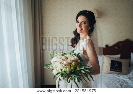 luxury bride in vintage dress with bouquet posing in luxury hotel room in morning. happy wedding couple, sensual romantic moment. long edge