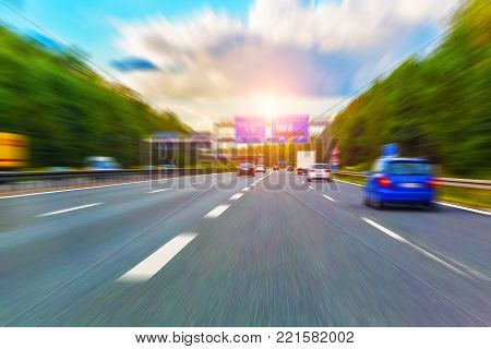 Driving the highway by car with traffic and motion blur effect at sunset