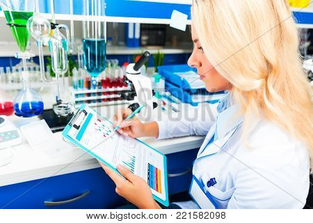 Young happy smiling attractive woman scientist in protective eyeglasses researching in the scientific chemical laboratory