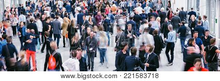 large crowd of business people walking in a floor on a trade fair. ideal for websites and magazines layouts