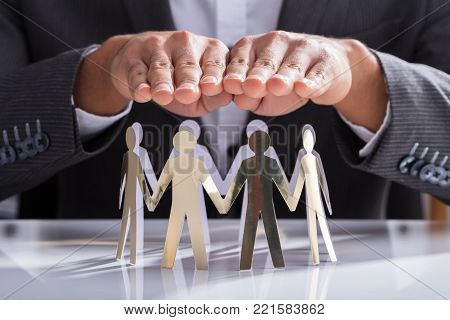 Close-up Of A Businessperson's Hand Protecting Cut-out Figures On Desk