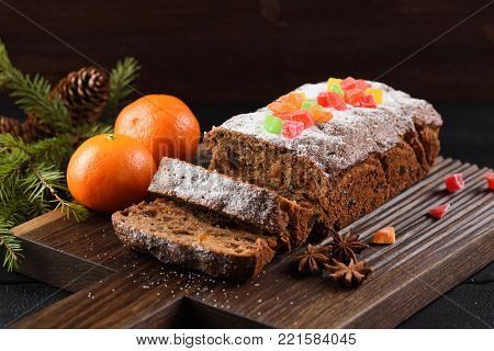 Traditional homemade chocolate fruit cake decorated with candied fruits, clementines, star anise and fir branch on carved dark oak board closeup