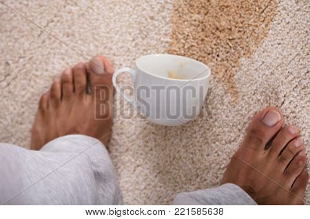 Close-up Of A Person's Feet Standing Near Spilled Coffee On Carpet