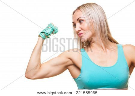 Athletic slender woman holding a measuring tape in the fist of her hand. The concept of will power, purposefulness