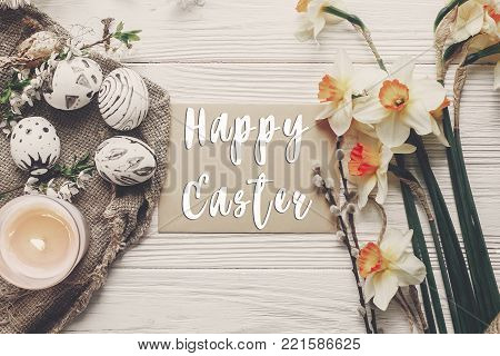happy easter text flat lay with flowers daffodils and stylish eggs on rustic wooden background top view. modern easter greeting card. space for text