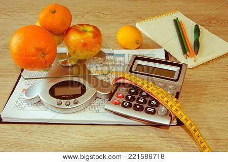 Diet plan. The concept of weight loss, wellness and healthy lifestyle. Vegetarian fruit diet. Products with low fat content. Fruits and measuring tape. Fruit dieting