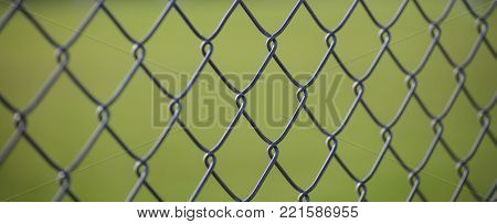 Wire mesh fence made of steel with green blurred background. Close up view with details, banner
