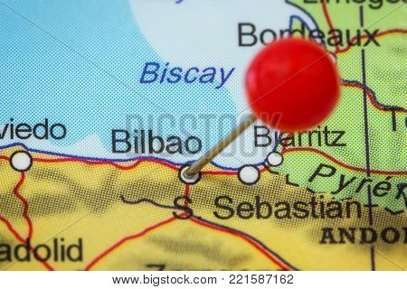 Close-up of a red pushpin in a map of Bilbao, Spain.