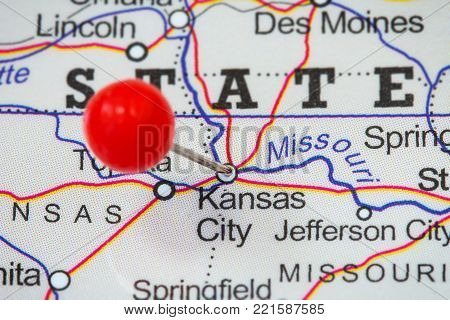 Close-up of a red pushpin in a map of Kansas City, USA.