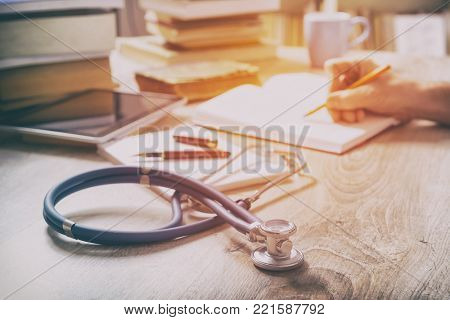 Young doctor is learning and preparing for the exam, he is using books and tablet to search for knowledge and making notes