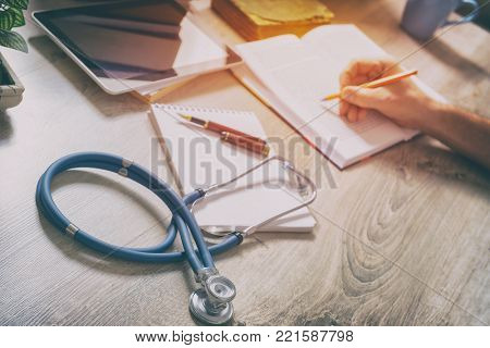 Young doctor is learning and preparing for the exam, she is using books and tablet to search for knowledge and making notes