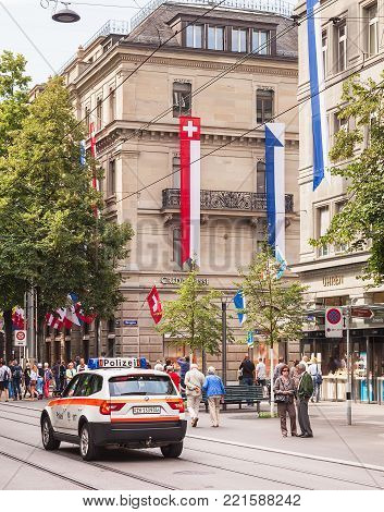 Zurich, Switzerland - 1 August, 2014: buildings on Bahnhofstrasse street decorated with flags for the Swiss National Day, people passing along the street. The Swiss National Day is the national holiday of Switzerland, celebrated on 1 August.