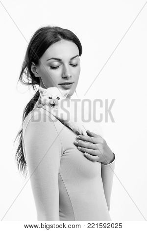 young woman or girl with pretty face in pink shirt holding little kitten fluffy domestic animal pet isolated on white background, copy space