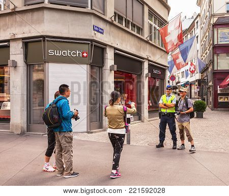 Zurich, Switzerland - 1 August, 2014: tourists making photo shooting with a policeman on Bahnhofstrasse street on the Swiss National Day. The Swiss National Day is the national holiday of Switzerland, celebrated on 1 August.