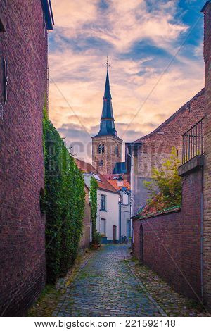 Narrow Brugge street. Classic Bruges city view. Sunset in Brugge.
