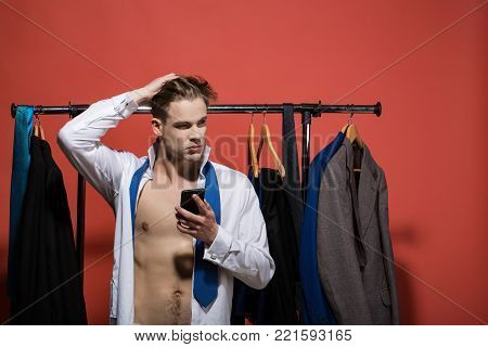 Business communication, new technology. Man with smartphone in open shirt and necktie. Fashion, style concept. Shopping, sale, purchase. Businessman use mobile phone in wardrobe on red background.