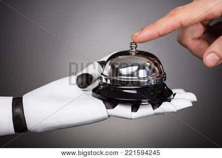 Person's Ringing Service Bell Hold By Robot On Grey Background