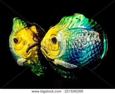 Closeup of a Glass Christmas Tree Ornament of a Colorful Fish Looking at its Reflection