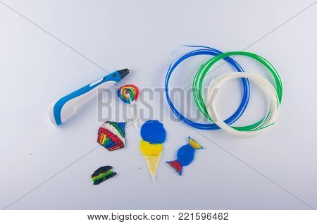 3d pen, blue, white, green plastic filaments, figures of cake, candy, ice cream, lollipop on white paper