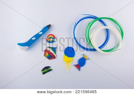 Colorful plastic cake, lollipop, candy, ice cream, made by 3D pen and white, blue, green filaments laying on white background