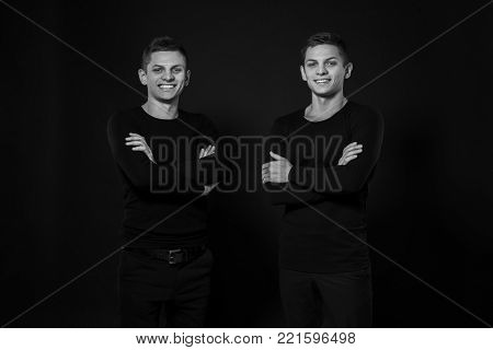 Casual twin brothers. Two brothers stand in the same positions. Studio shot. Black and white photography