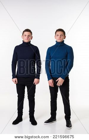 Casual twin brothers. Two brothers stand in the same positions. Studio shot on a white background