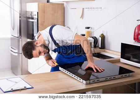 Male Electrician Fixing Induction Stove With Screwdriver